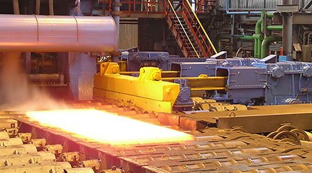 A steel sheet being transported in a hot steel mill production.